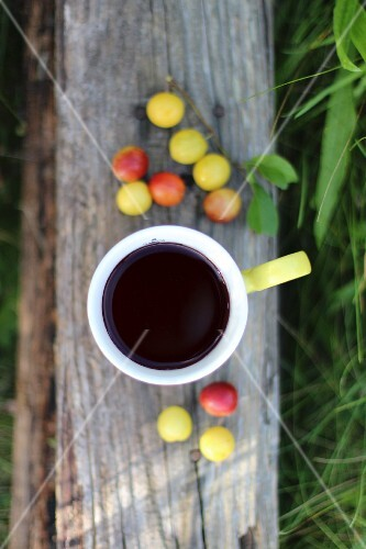 Coffee and mirabelle plums on plank of wood