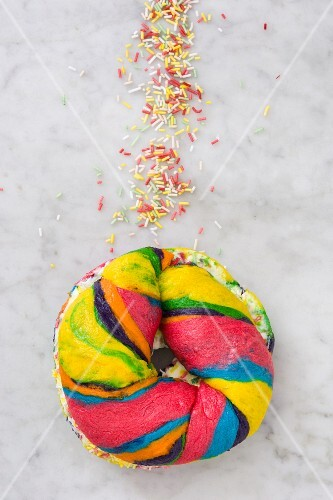 A colourful bagel with cream cheese and sprinkles