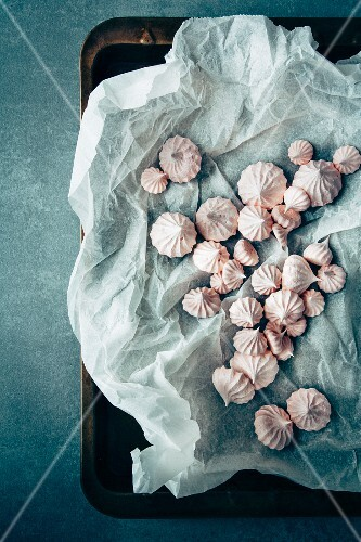 Mini meringues with paper on a baking tray