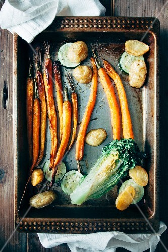 Roast potatoes, carrots, lettuce and courgette with thyme on a baking tray