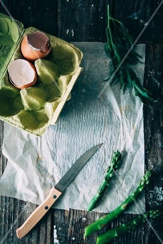Green asparagus, egg shells in an egg box and fresh tarragon