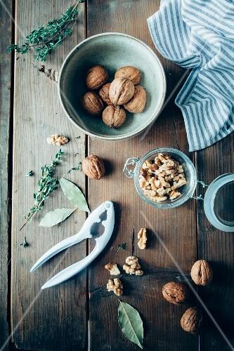 Walnuts, fresh thyme, bay leaves and a nutcracker