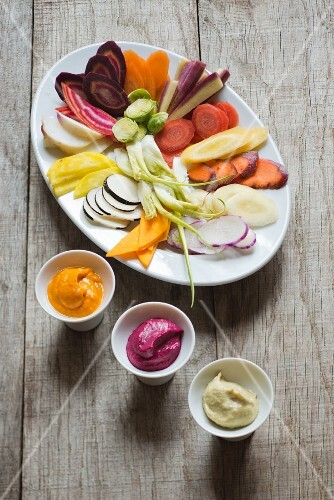 A plate of raw winter vegetables with three vegetable dips