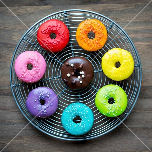 Colorful glazed donuts on a wire rack