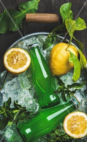 Bottles of green lemonade on chipped ice in metal tray with fresh lemons