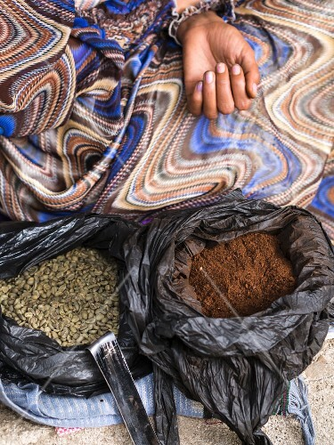 Bags of green Ethiopian coffee beans and ground coffee used in the coffee ceremony.