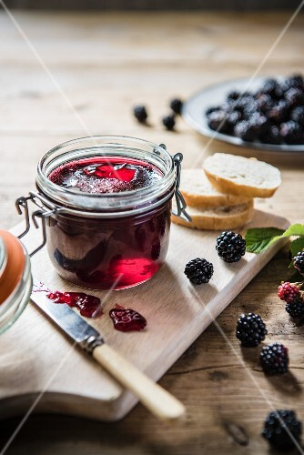 A jar of home-made blackberry jam with fresh blackberries and bread