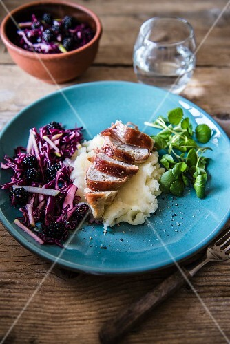Chicken breast wrapped in bacon on a bed of mashed potatoes with red cabbage & blackberry coleslaw and watercress