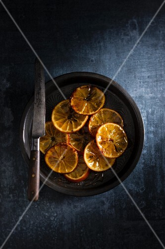 Candied orange slices on a plate with a knife