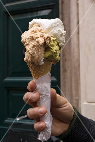 A hand holding an ice cream cone with pistacho & rum ice cream and cream