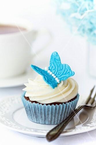 Schokoladen-Cupcake, dekoriert mit einem blauen Zucker-Schmetterling
