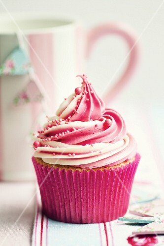 Cupcake decorated with a swirl of strawberry and vanilla frosting