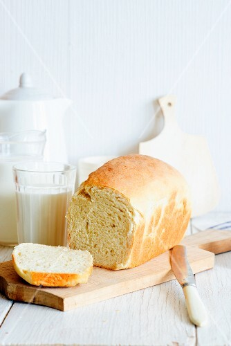 A sliced loaf od home-made milk bread on a chopping board