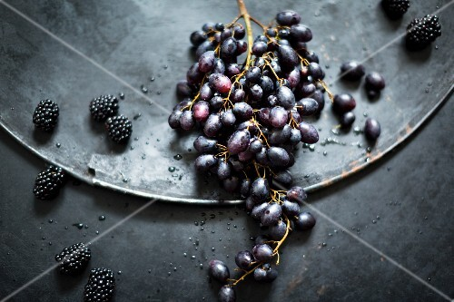 An arrangement with red grapes and blackberries on an old metal surface