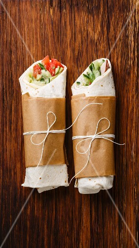 Tortilla wraps sandwiches with fresh vegetables on wooden background