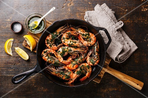 Tiger prawns roasted on frying grill pan with green sauce, lemon and garlic on wooden background