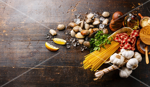 Dark wooden background with Ingredients for cooking Spaghetti vongole