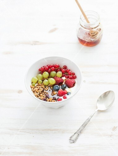 Oat granola crumble with fresh fruit, berres, honey in bowl over white painted wooden background