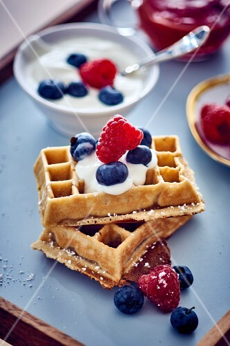 A waffle with cherries with blueberries