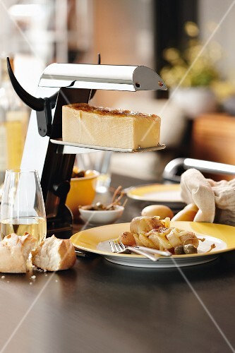 Cheese in a raclette stand next to raclette with potatoes and capers