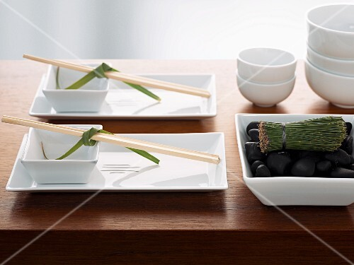 A Japanese table setting with a tea whisk and bowls