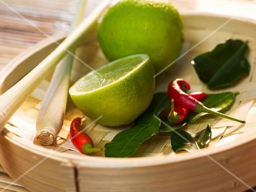 Lemongrass, lime, lemon leaves and chilli peppees on a bamboo steamer