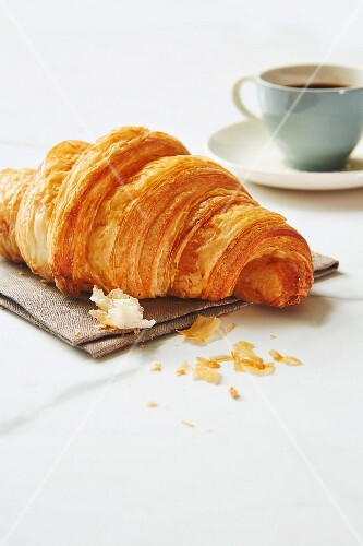 A croissant with an espresso cup in the background