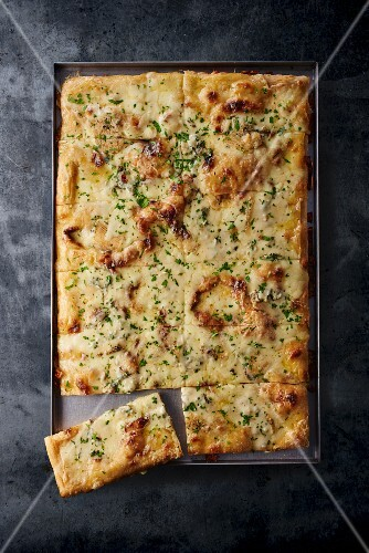 Four-cheese pizza on a baking tray