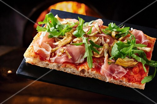 A pizza with bacon, artichoke and rocket