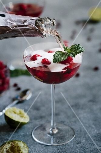 A glass of Raspberry and Pomegranate Champagne Cocktail is being topped of with champagne