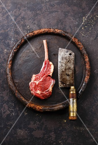 Raw fresh meat Veal ribs and Meat cleaver on stone plate on dark background