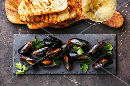 Mussels on stone slate, Bread toasts and Wine on dark background