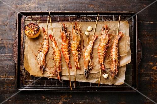 Grilled fried Tiger prawns shrimps on skewers and lemon on metal grid baking sheet background