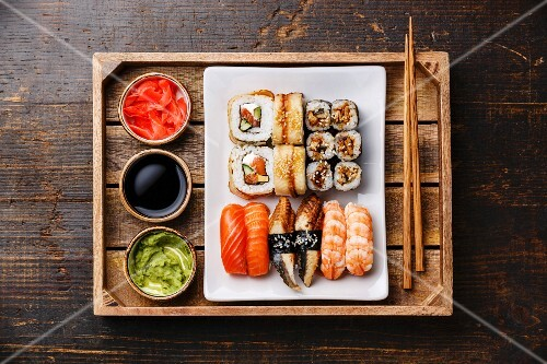 Sushi Set nigiri and rolls with chopsticks, ginger, soy sauce and wasabi in tray on rustic wooden background