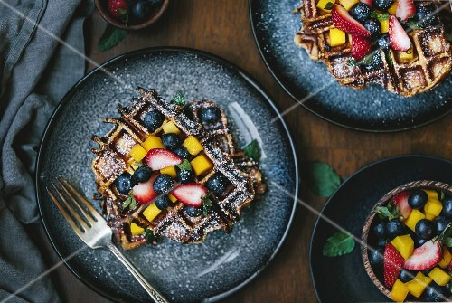 Two plates of brioche waffles are topped off with fruit and dusted with powdered sugar