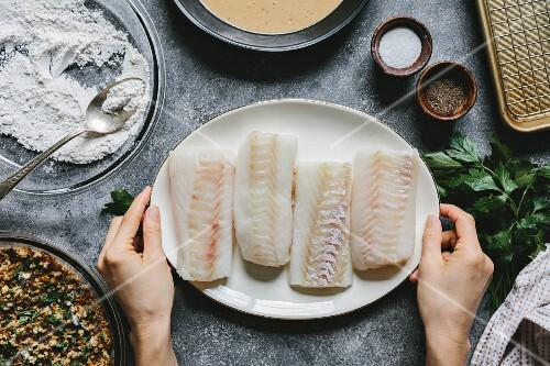 A woman is placing four cod fillets on the table