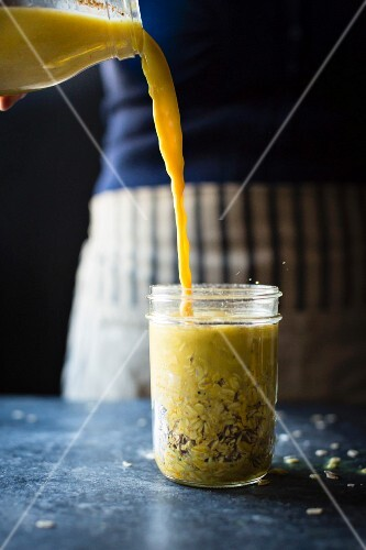 A woman pouring golden milk on to oats in a jar