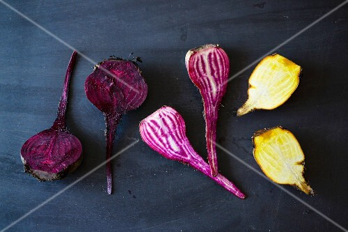 Yellow and purple beetroots on a dark surface