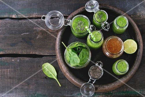 Spinach smoothie in glass jars served with spinach leaves, chia seeds, honey and lime