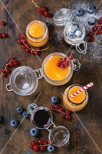 Melon and berry smoothies with yoghurt in glass jars