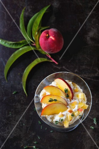 A ricotta dessert with peach, thyme and honey served in a cocktail glass