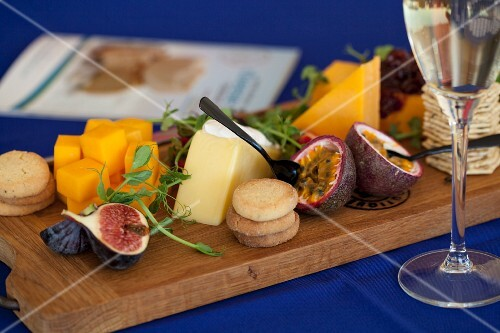 A cheeseboard with biscuits, figs and watercress