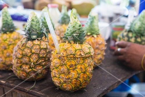 Pineapples with their tops sliced off with straws at a market
