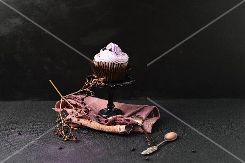A cupcake with an elderberry topping