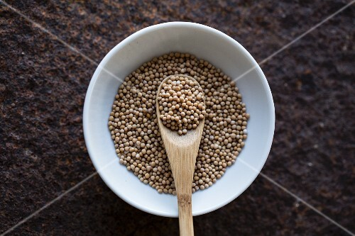 Mustard seeds with a wooden spoon in a bowl (seen from above)