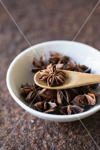 Star anise with a wooden spoon in a bowl