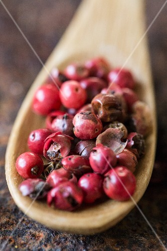 Red peppercorns on a wooden spoon (close-up)