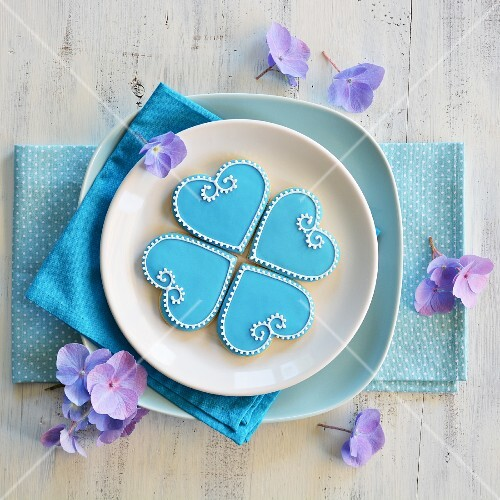 Four heart-shaped biscuits decorated with blue and white icing