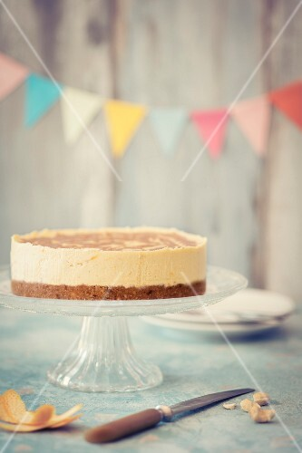 Raw vegan cheesecake on a cake stand with bunting in the background