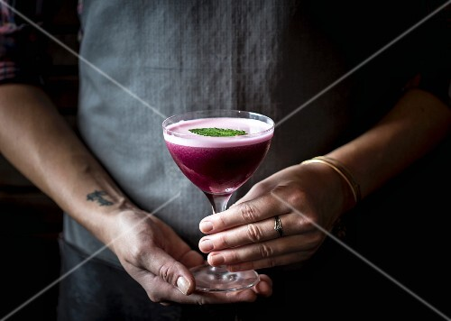 A woman holding a blueberry cocktail in a stemmed glass
